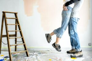 Couple hugging in a room with painting equipment