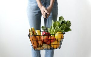 Woman holding a shopping basket full of vegetables