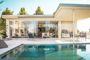 Modern home exterior, glass walls with pool and patio kitchen